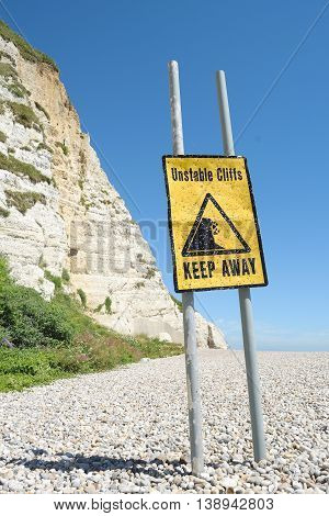 Warning sign in a front of the white cliff on Jurassic Coast