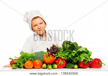 Happy kid boy in cook's uniform, preparing healthy vegetables meal, isolated on white background