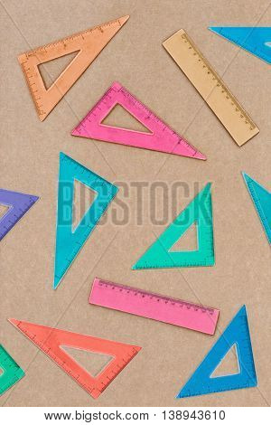 Overhead shot of arranged colorful set squares on brown paper