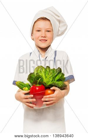 Close-up picture of young smiling cook, holding bowl of fresh vegetables, isolated on white