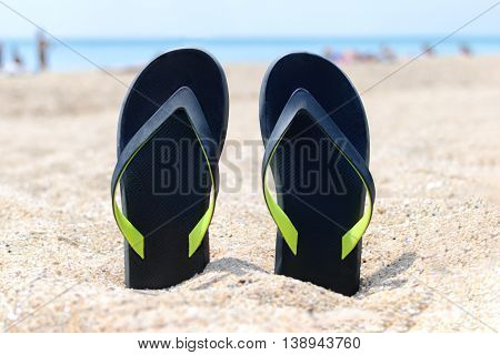a pair of flip-flops stuck on the sand of a beach