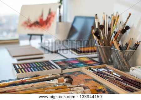 Painter workplace in order side view. Designer desk with drawing equipment. Home studio for artist.