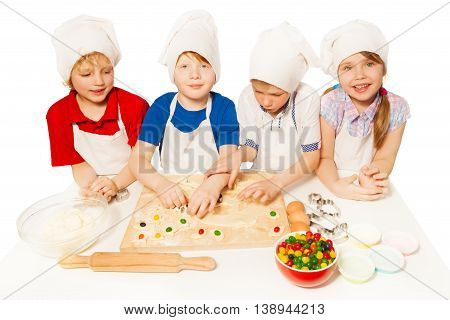 Four little bakers, kids in aprons and toques standing in row, preparing candy filled cookies, isolated on white