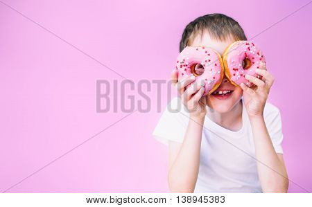 boy looking through pink donuts. child holding a donuts in two eyes like glasses and having fun. pink background. isolated. empty space for your text