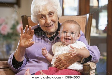 Grandmother holding her granddaughter on lap