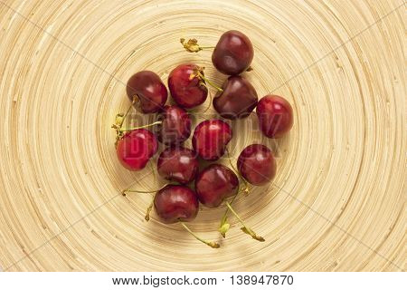 A photo of bright cherries shot from above on a bamboo plate with copyspace