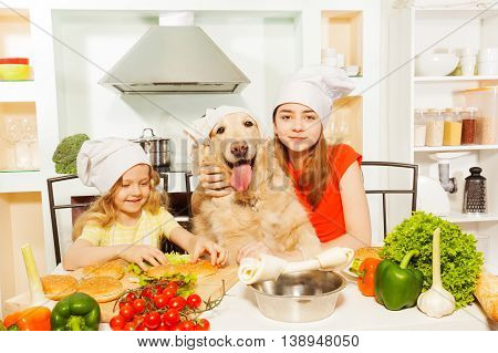 Two age-diverse girls, sisters in cook's hats, making hamburgers with their pet in the kitchen