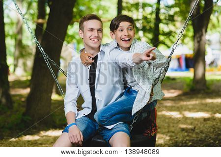 Smiling boys having fun at playground. Children playing outdoors in summer. Teenagers riding on a swing.