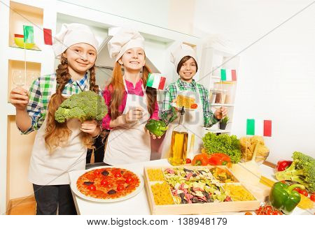 Three young Italian cooks, girls and boy in aprons and cook's hats, demonstrating traditional Italian food at the kitchen