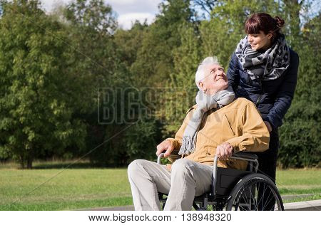 Woman Supporting Man On Wheelchair