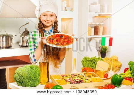 Cute young Italian girl in cook's uniform holding plate with tasty pizza in the kitchen full of kitchen-stuff