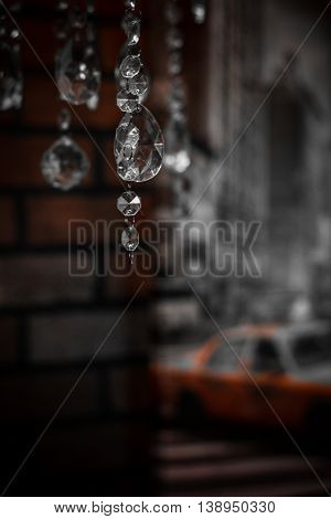 Chandelier glass hangs in the foreground against a backdrop of blurred brick wall and street life