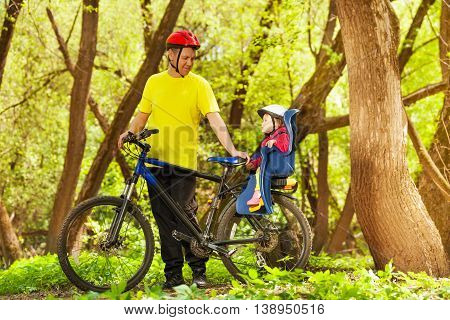Side view picture of active father and his little toddler daughter riding a bike together in the spring park