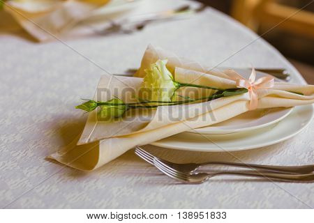 Spring table decoration with flowers. White plates, forks, knifes
