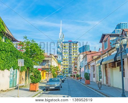 The street of the old town with the white modern clock tower on background Batumi Georgia.