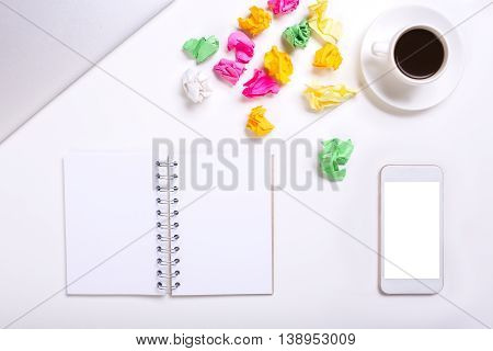 Top view of messy white office desktop with colorful crumpled paper blank spiral notepad smart phone coffee cup and closed laptop. Mock up