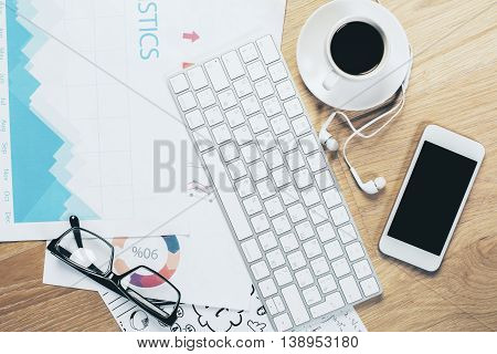 Top view of wooden office desktop with blank mobile phone and headphones keyboard glasses business report and coffee cup. Mock up