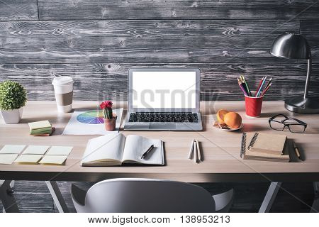 Front view of creative designer workplace with blank white laptop stationery items lamp orange and chocolate on plate and other items on wooden background. Mock up