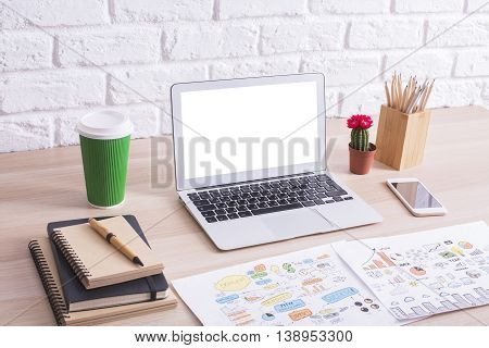 Side view of creative designer desktop with blank white laptop screen business sketch coffee cup cactus and other items on white brick wall background. Mock up