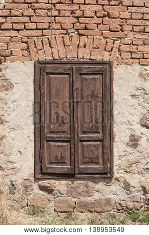 Window of old village house with brown wooden shutters closed