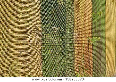Metal mesh fence wall painted in green and yellow closeup as background