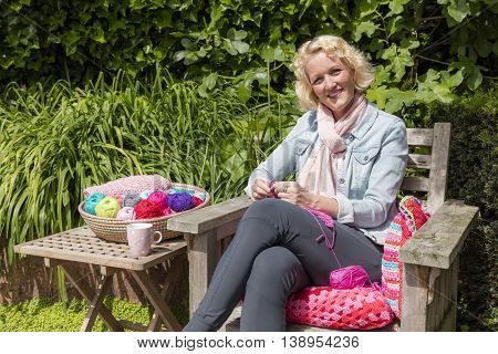 Young Blond Woman Crochets In The Garden