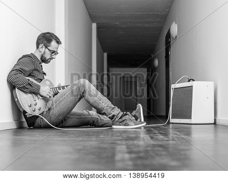 Photo of a man sitting playing his electric guitar in front of a small combo amplifier in a hallway. Black and white version.
