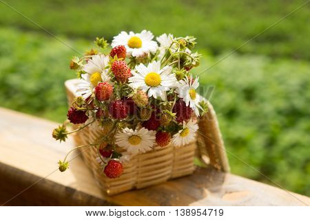Basket of fresh ripe sweet strawberries with daisies bouquet selective focus