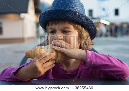 Cute little boy with huge appetite sitting at the table devours tasty croissant.