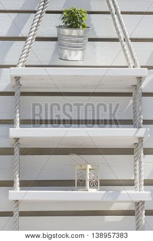 Close up of a decorative white wooden boards wall with a nice shelves made of ropes and wooden boards and a lantern and tin can with herbs placed on it