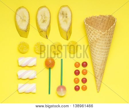 Creative photo of a waffle cone with fruits and sweets on yellow background.