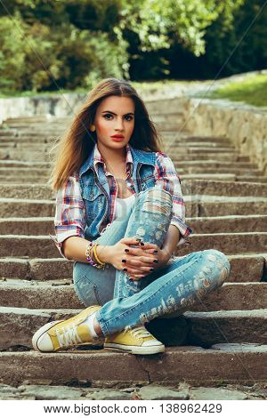 Beautiful young woman dressed in jeans posing on a concrete staircase