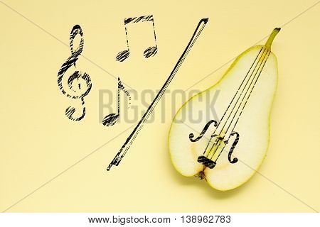 Creative concept photo of a pear as a violin with illustrated bow and notes on yellow background.