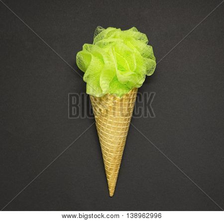 Creative concept photo of a waffle cone with a bath puff on black background.