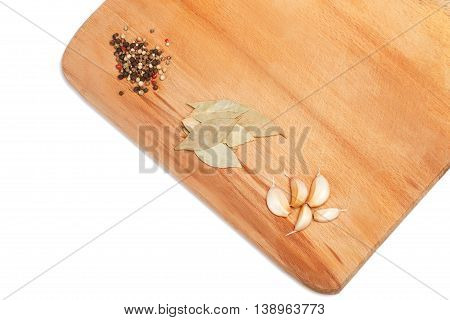 Garlic paprika and bay leaf on wooden cutting board over white background