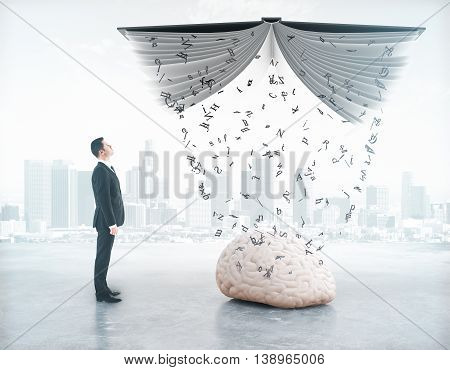 Businessman looking at letters pouring out of book into brain on abstract city background. Education concept. 3D Rendering