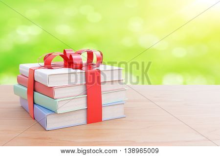 Wooden surface with stack of colorful book tied up with a ribbon as a present on abstract green background. 3D Rendering