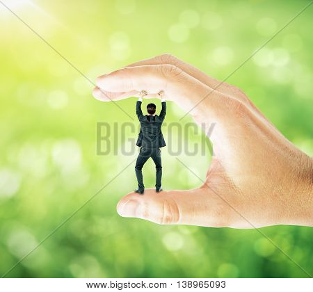 Businessman trapped between fingers of big hand on abstract green background. Pressure concept