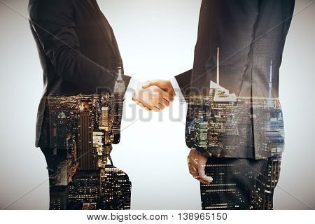 Businesspeople shaking hands on grey city background. Double exposure