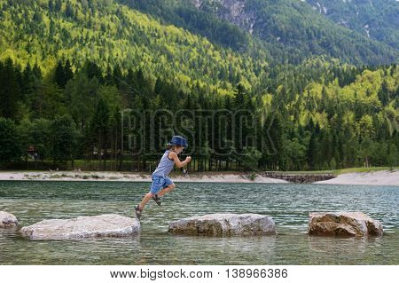 Adorable young boy with a hat crossing river or water jumping from rock to rock. Crossing the gap freedom liberation success avoiding danger courage concept