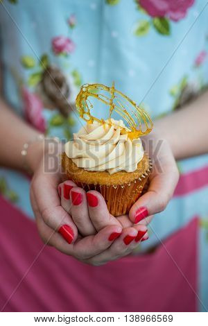 Woman In Floral Dress With Painted Nails Holding Toffee Cupcake
