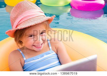 Smiling Blond Girl Floating On Yellow Inner Tube