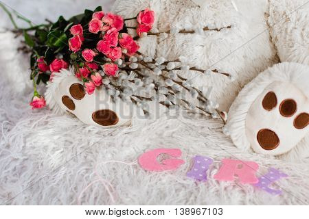 A Beautiful Soft Toy Bear Sits On The Bed With Flowers