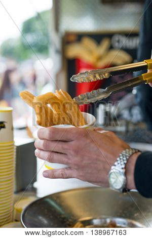 Mans Hands Serving Churros With Tongs In A Paper Cup