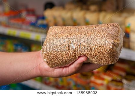 Packages with a buckwheat hand to the buyer at the store