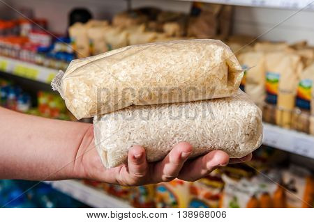 Bags of rice at the buyer's hand in the store