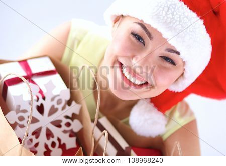 Happy girl on santa hat holding a shopping bag with gift box