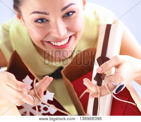 Smiling woman with christmas gifts, isolated on red background