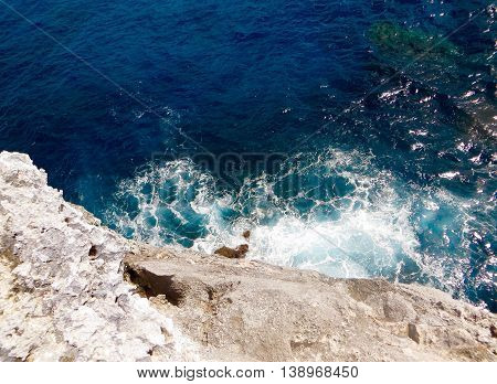 Looking down from a rock cliff into the deep-blue Atlantic ocean waves crashing against the rocks