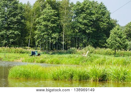 Beautiful view of lake, fishing rod, green forest , blue sky